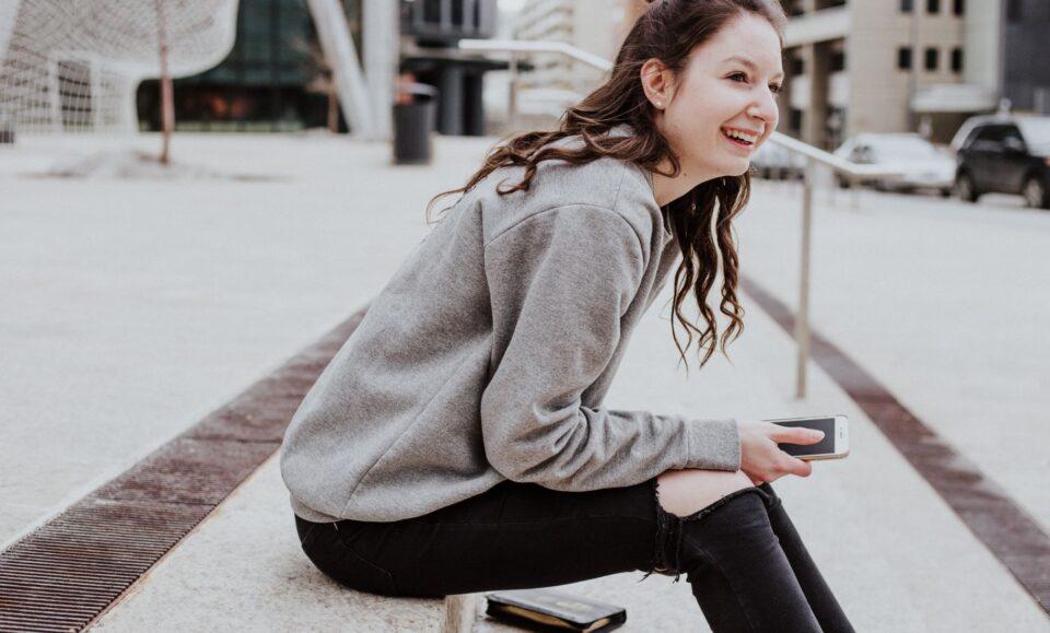 Ung kvinde sidder med smartphone i hånden
